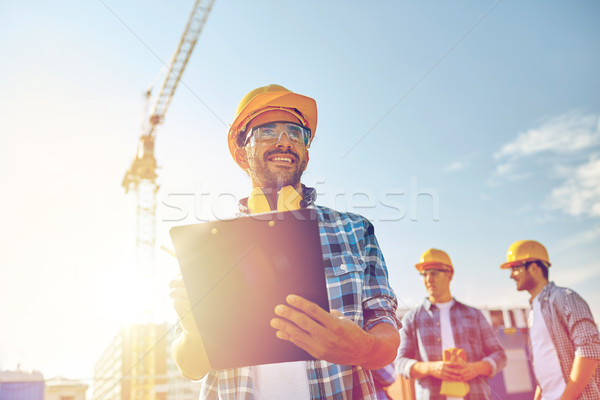 builder in hardhat with clipboard at construction Stock photo © dolgachov