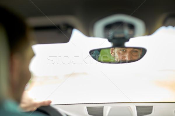 rearview mirror reflection of man driving car Stock photo © dolgachov