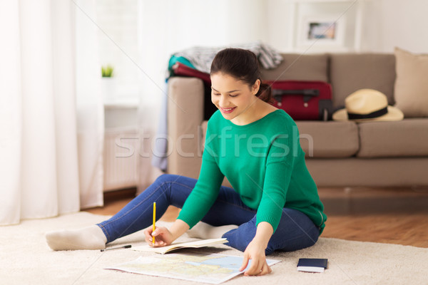 woman with notebook and travel map at home Stock photo © dolgachov