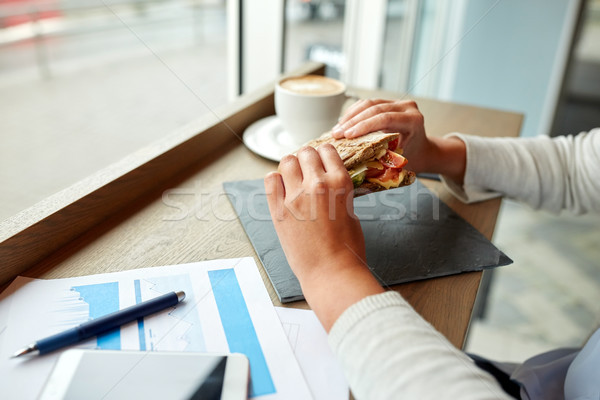Stock photo: woman eating salmon panini sandwich at cafe