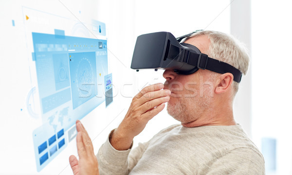 old man in virtual reality headset or 3d glasses Stock photo © dolgachov
