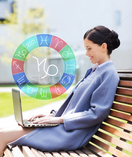 smiling woman with laptop and zodiac signs in city Stock photo © dolgachov