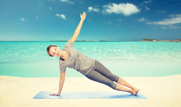woman making yoga in side plank pose on beach  Stock photo © dolgachov