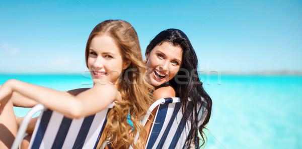 Felice donne prendere il sole sedie blu mare Foto d'archivio © dolgachov