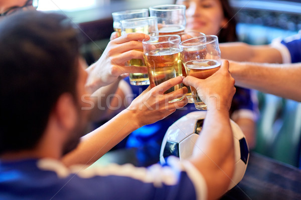 football fans clinking beer glasses at sport bar Stock photo © dolgachov