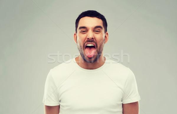 Férfi mutat nyelv szürke gorombaság emberek Stock fotó © dolgachov