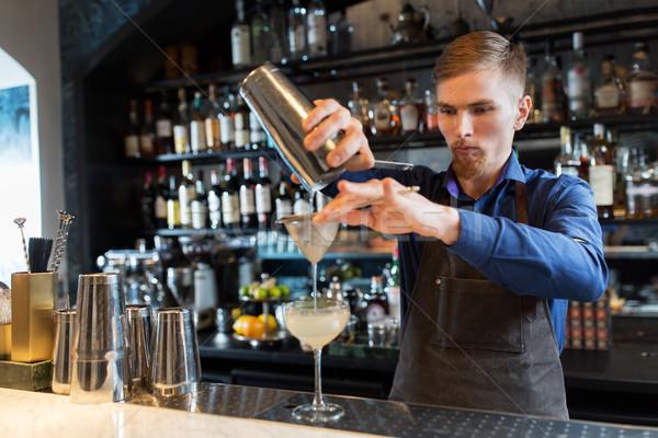 barman with shaker preparing cocktail at bar Stock photo © dolgachov