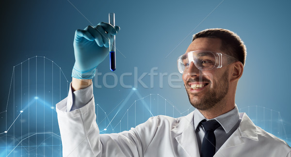 scientist in goggles with test tube and diagram Stock photo © dolgachov