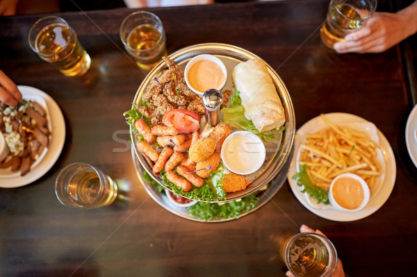 table with food and beer glasses at bar or pub Stock photo © dolgachov
