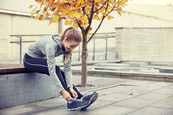 happy young sporty woman tying shoelaces outdoors Stock photo © dolgachov