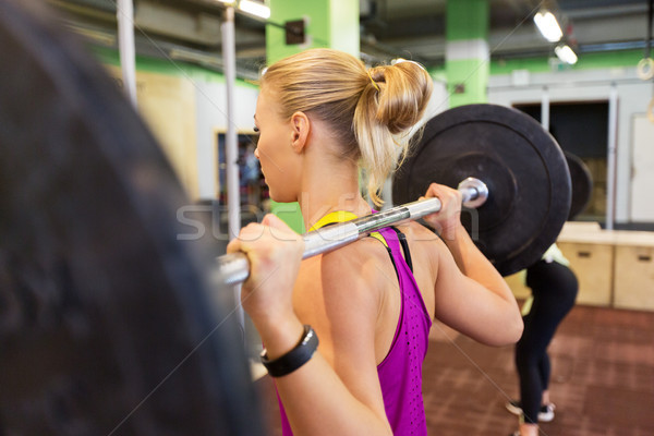 woman with barbell at group training in gym Stock photo © dolgachov