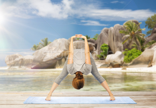 woman doing yoga wide-legged forward bend on beach Stock photo © dolgachov