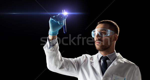scientist in safety glasses with test tube Stock photo © dolgachov