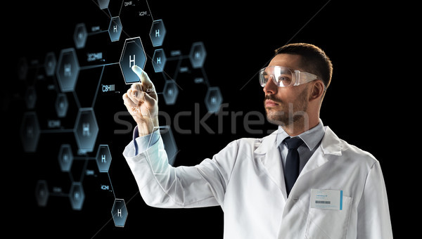 scientist in goggles with chemical formula Stock photo © dolgachov