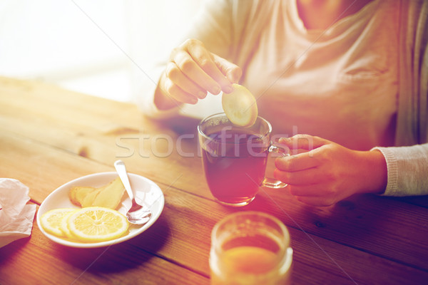 close up of woman adding lemon to tea cup Stock photo © dolgachov