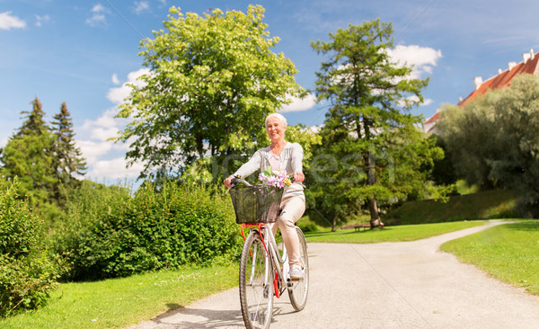 happy senior woman riding bicycle at summer park Stock photo © dolgachov