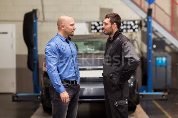 auto mechanic talking to customer at car shop Stock photo © dolgachov