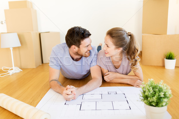 couple with boxes and blueprint moving to new home Stock photo © dolgachov