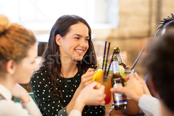 happy friends clinking drinks at bar Stock photo © dolgachov