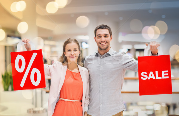 happy young couple with red shopping bags in mall Stock photo © dolgachov