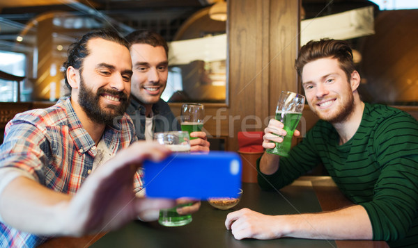 friends taking selfie with green beer at pub Stock photo © dolgachov