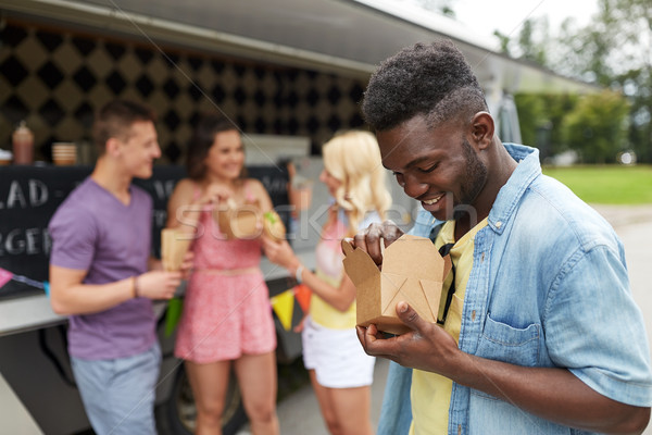 happy man with wok and friends at food truck Stock photo © dolgachov