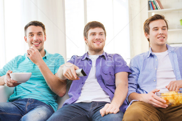 happy male friends watching tv at home Stock photo © dolgachov