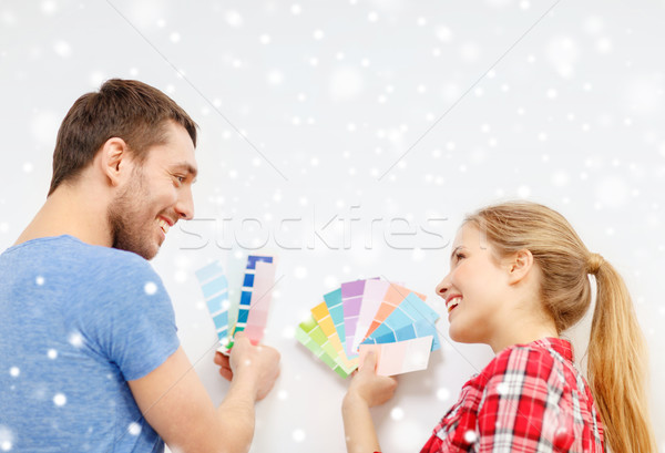 smiling couple selecting color from samples Stock photo © dolgachov