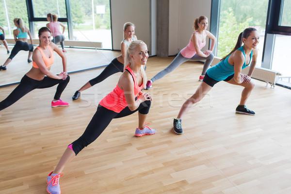 group of women making lunge exercise in gym Stock photo © dolgachov