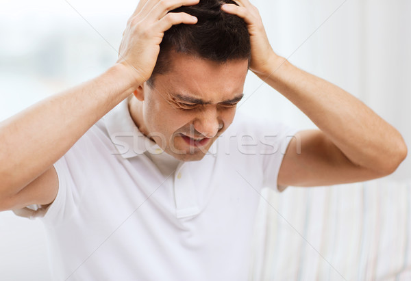 unhappy man suffering from head ache at home Stock photo © dolgachov