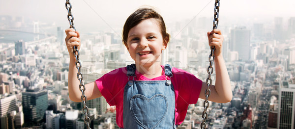 happy little girl swinging on swing over city Stock photo © dolgachov