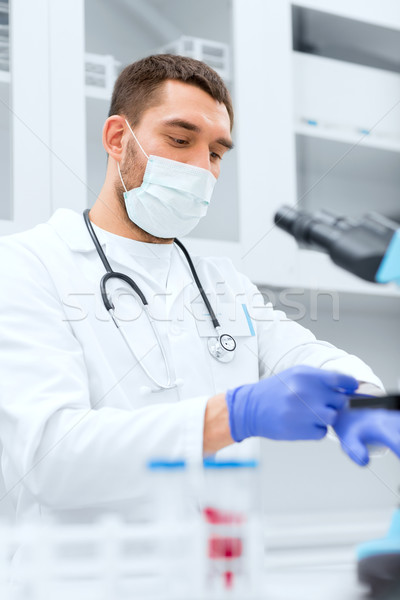 young male scientist wearing gloves in lab Stock photo © dolgachov