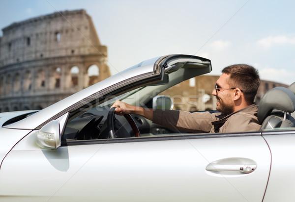 happy man driving cabriolet car over coliseum Stock photo © dolgachov
