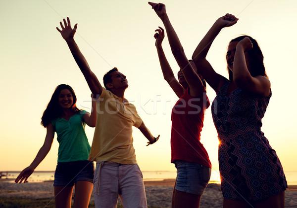 smiling friends dancing on summer beach Stock photo © dolgachov