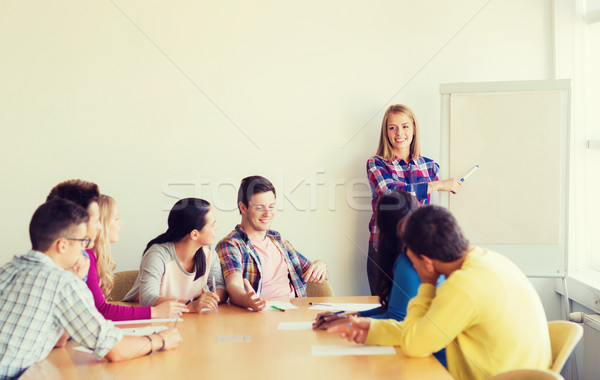 group of smiling students with white board Stock photo © dolgachov