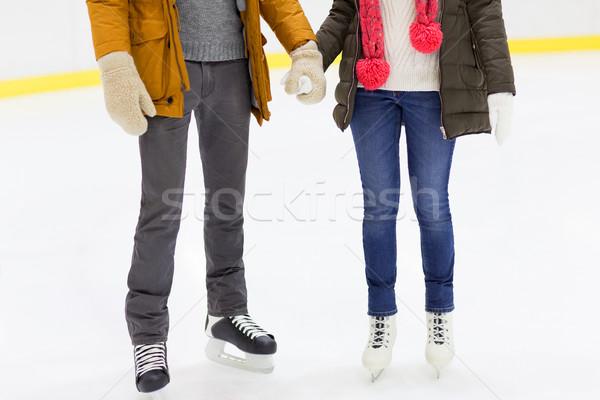 close up of happy couple skating on ice rink Stock photo © dolgachov