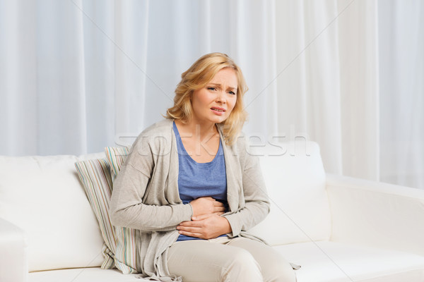 Stock photo: unhappy woman suffering from stomach ache at home