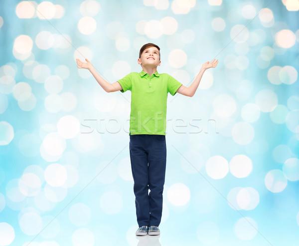 happy boy in polo t-shirt raising hands up Stock photo © dolgachov