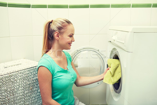 happy woman putting laundry into washer at home Stock photo © dolgachov