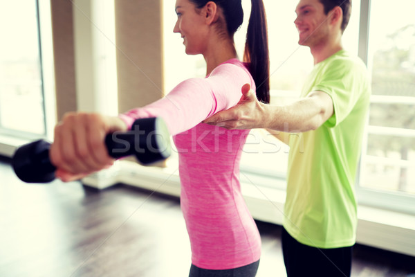 Stock photo: smiling young woman with personal trainer in gym
