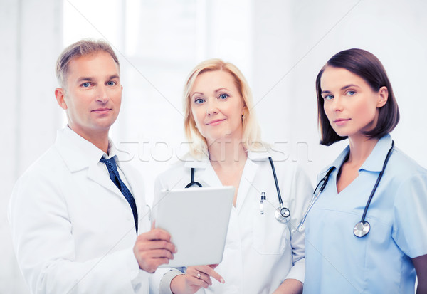 doctors looking at tablet pc Stock photo © dolgachov