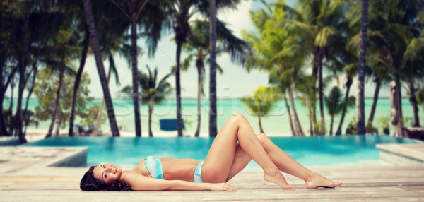 happy woman in bikini tanning over summer beach Stock photo © dolgachov
