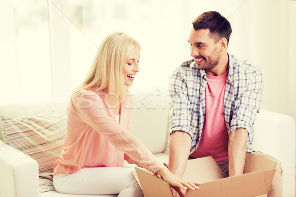 happy couple with open parcel box at home Stock photo © dolgachov