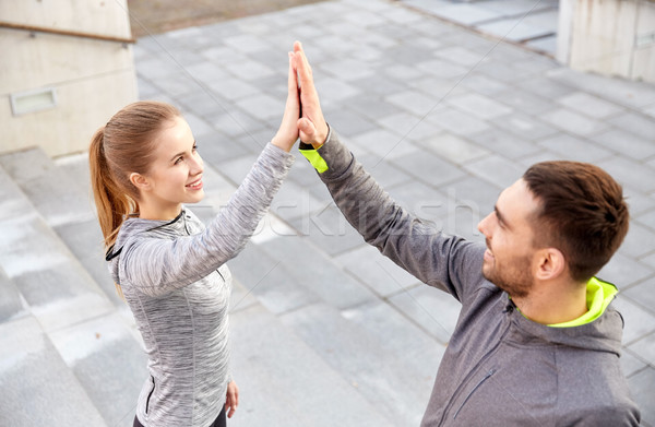 smiling couple making high five on city street Stock photo © dolgachov