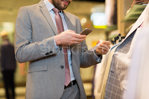 close up of man with smartphone at clothing store Stock photo © dolgachov