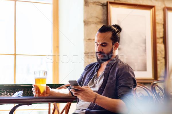 Uomo smartphone bere birra bar pub Foto d'archivio © dolgachov