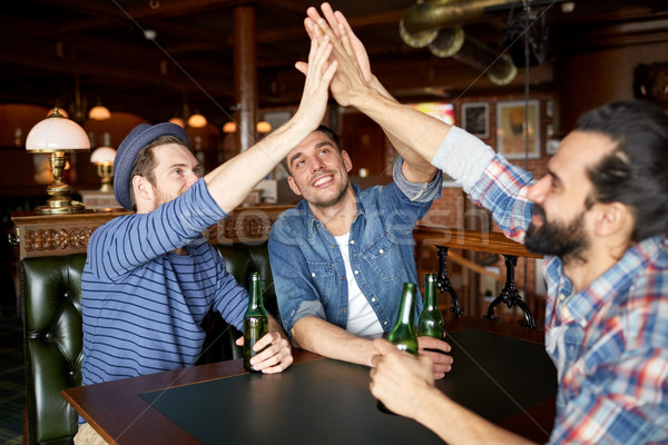 men with beer making high five at bar or pub Stock photo © dolgachov