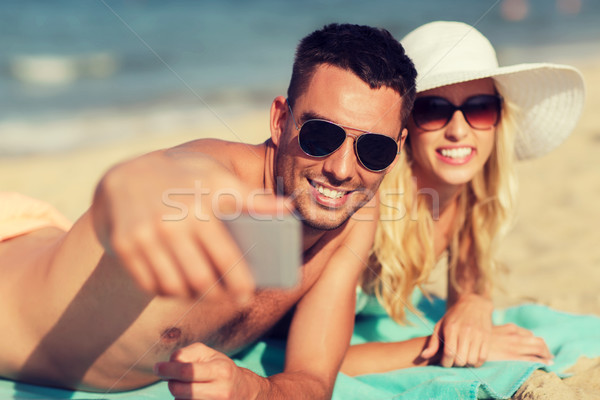 happy couple in swimwear walking on summer beach Stock photo © dolgachov
