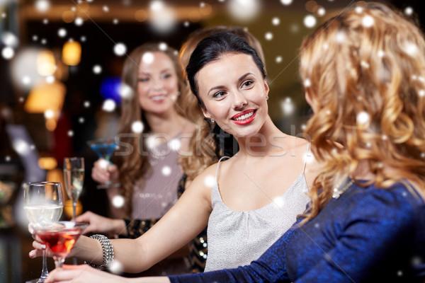 happy women with drinks at night club over snow Stock photo © dolgachov