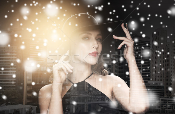 beautiful woman in black hat over city and snow Stock photo © dolgachov